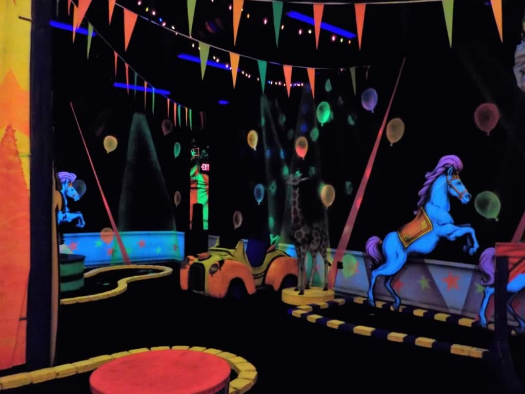 The use of black-lights helps add to the circus atmosphere at this indoor mini-golf course.