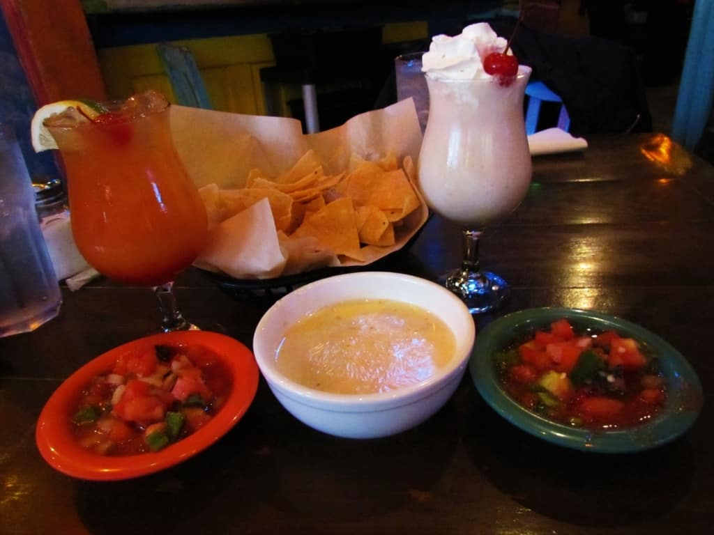 Some Queso dip and salsa with tortilla chips pairs well with a couple of house specialty drinks.