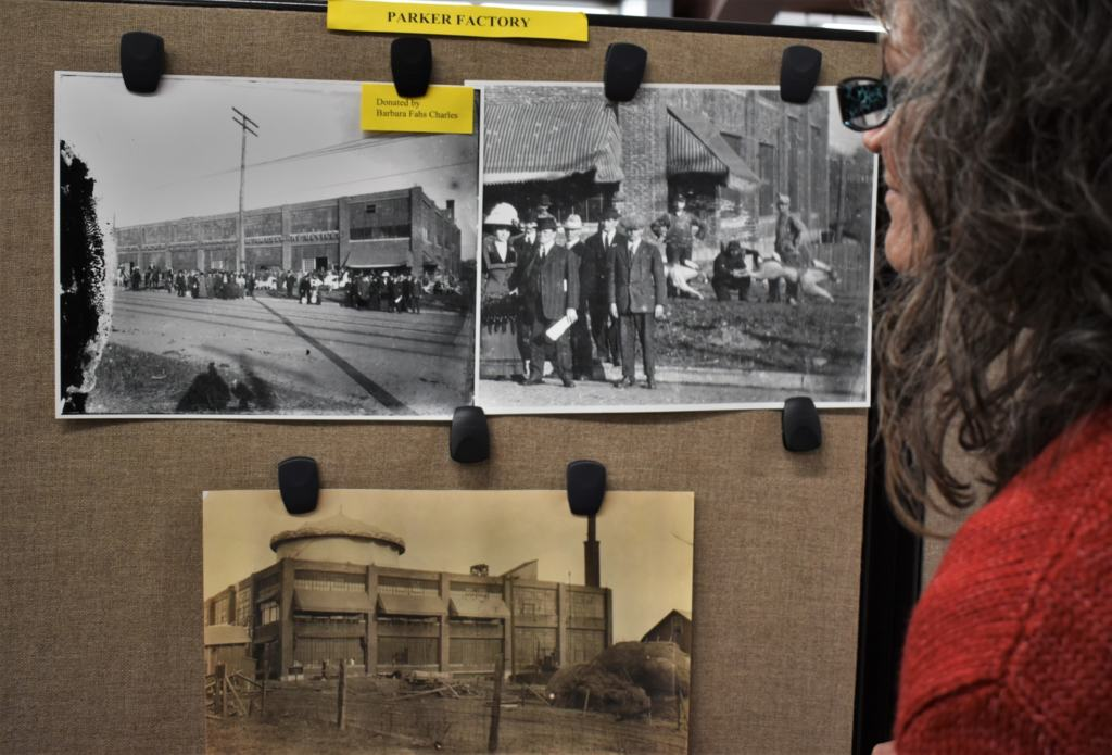 Crystal examines photos of the Parker factory in Leavenworth, Kansas.