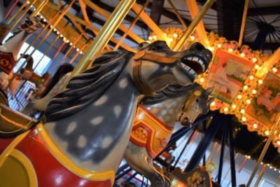 A permanent whinny resides on the face of a beautifully carved wooden carousel horse.