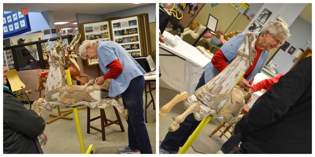 A volunteer works diligently at repairing years of damage to a carousel horse.