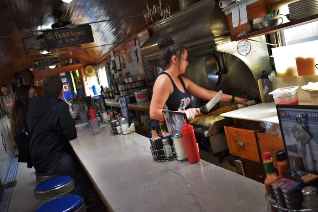 The fry cook loads the griddle with over-sized servings of food at Franks' Diner.