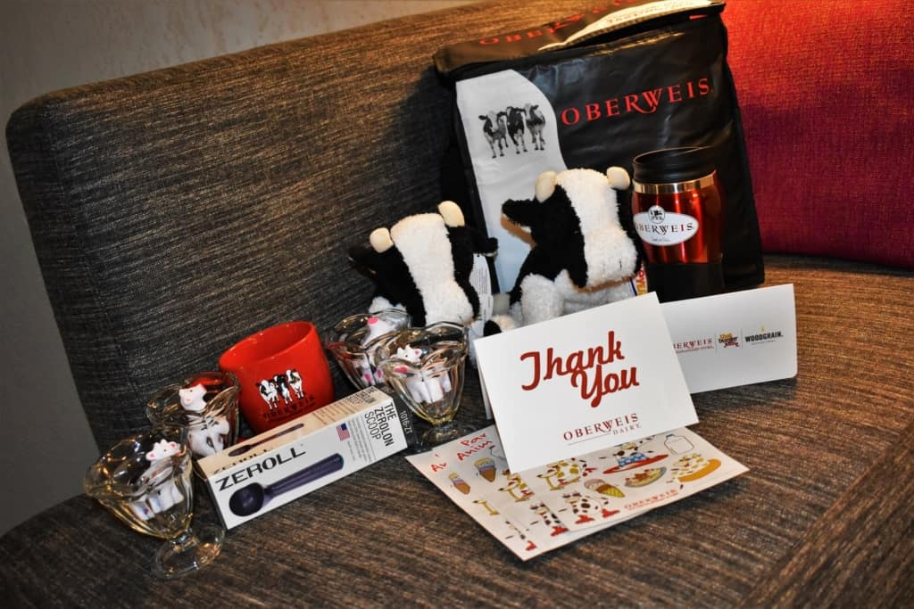 A swag bag from Oberweis Dairy is packed full of logo'd items.