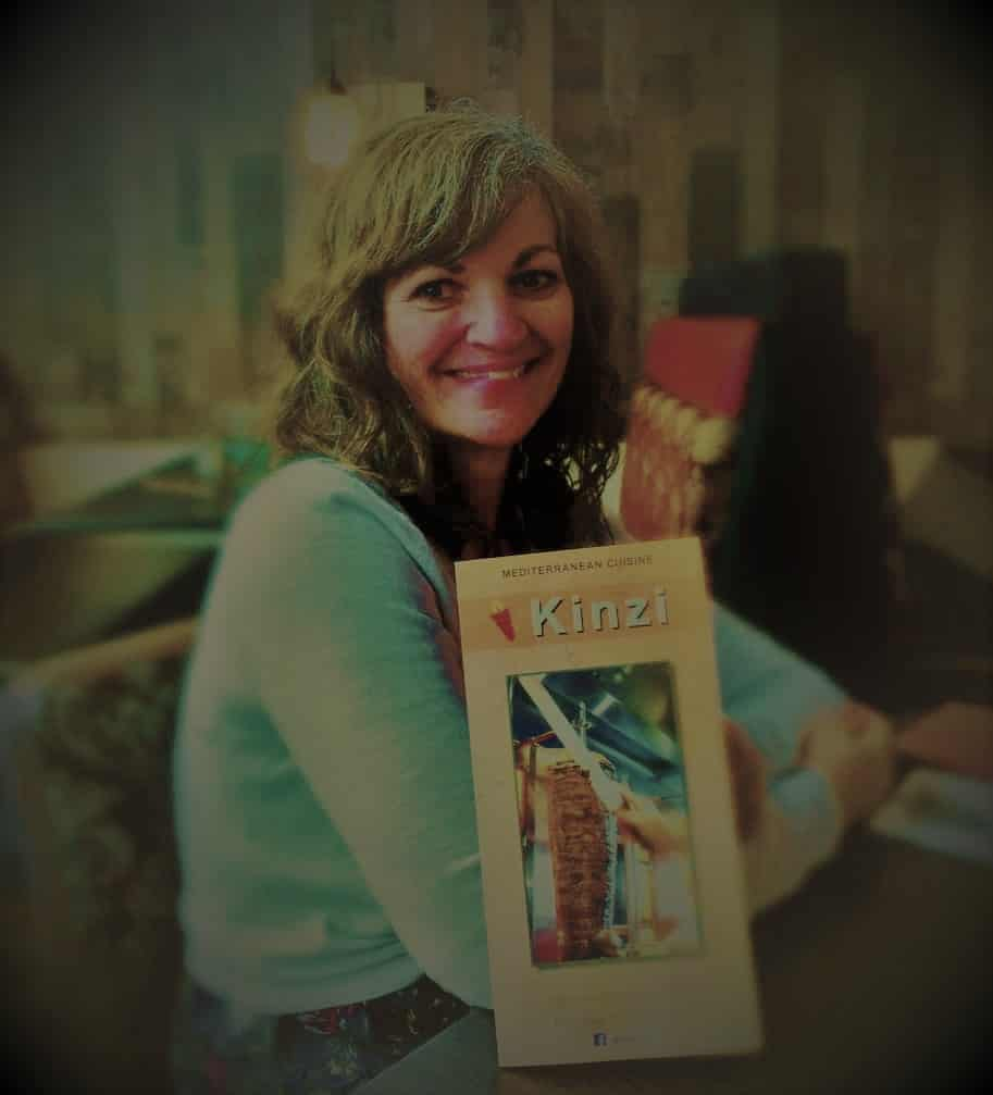Crystal poses with a menu from Kinzi Restaurant in Mission, Kansas.