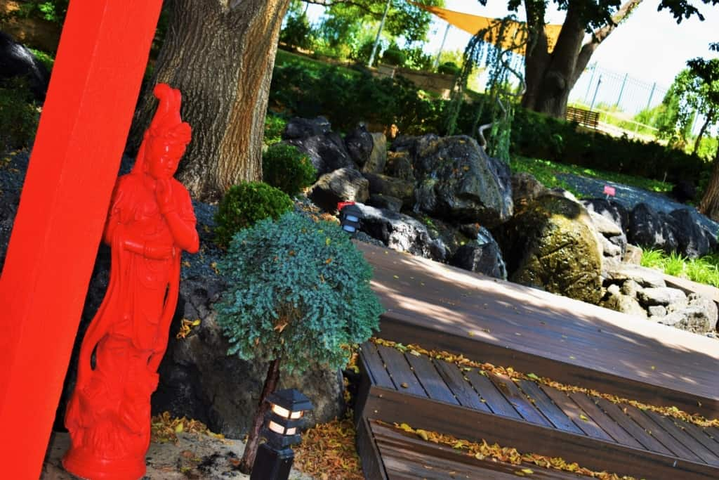 The bright red statues add contrast to the various shades of green found at the Amarillo Botanical Gardens.