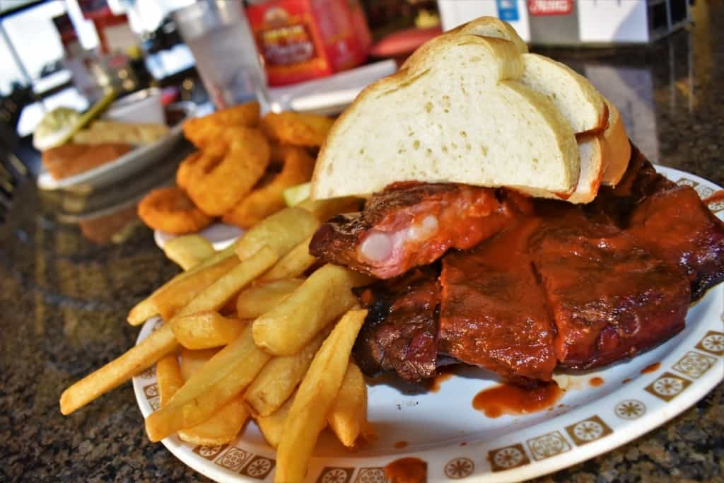 A plate of barbecue ribs pair well with french fries and onion rings.