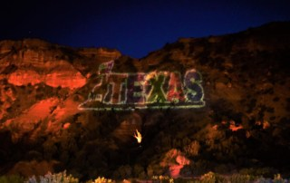 As the darkness grows, the Texas logo appears on the canyon wall.