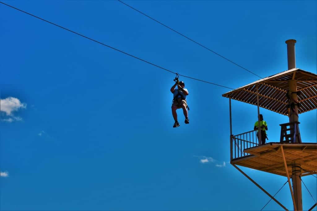 The author zip-lines across a gorge in Palo Duro canyon.