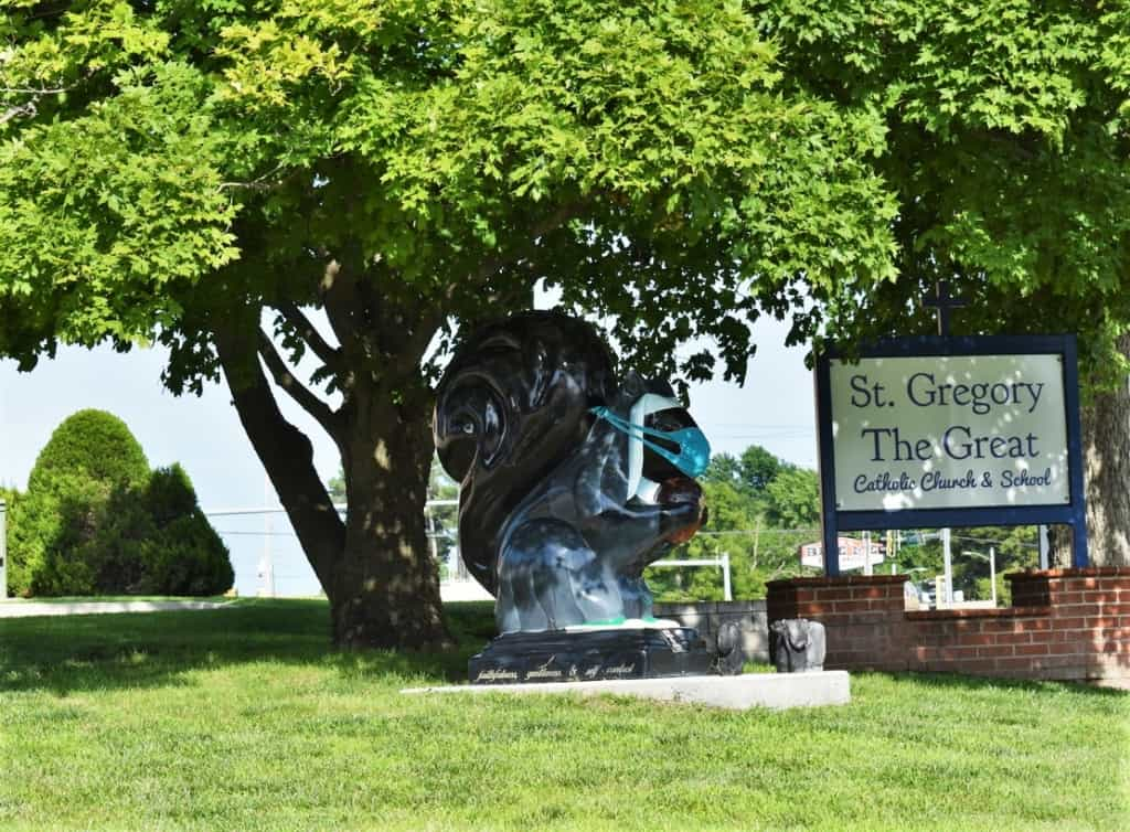 An iconic black squirrel statue rests near the entrance to a local Catholic school.