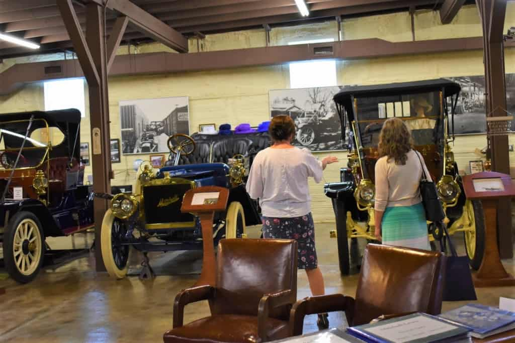 Katie explains some history about the vehicles at the Mitchell Car Museum.