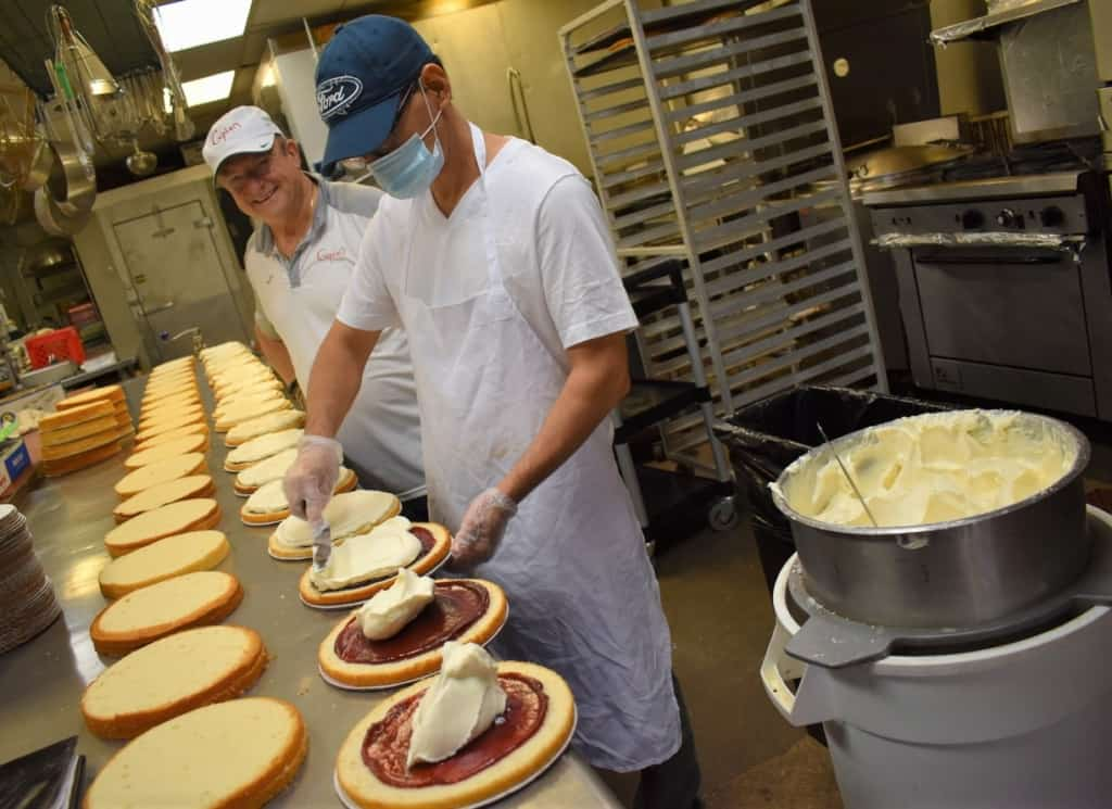 Franco Cupini watches over a staff member who works at assembling some of the amazing desserts offered at Cupini's.