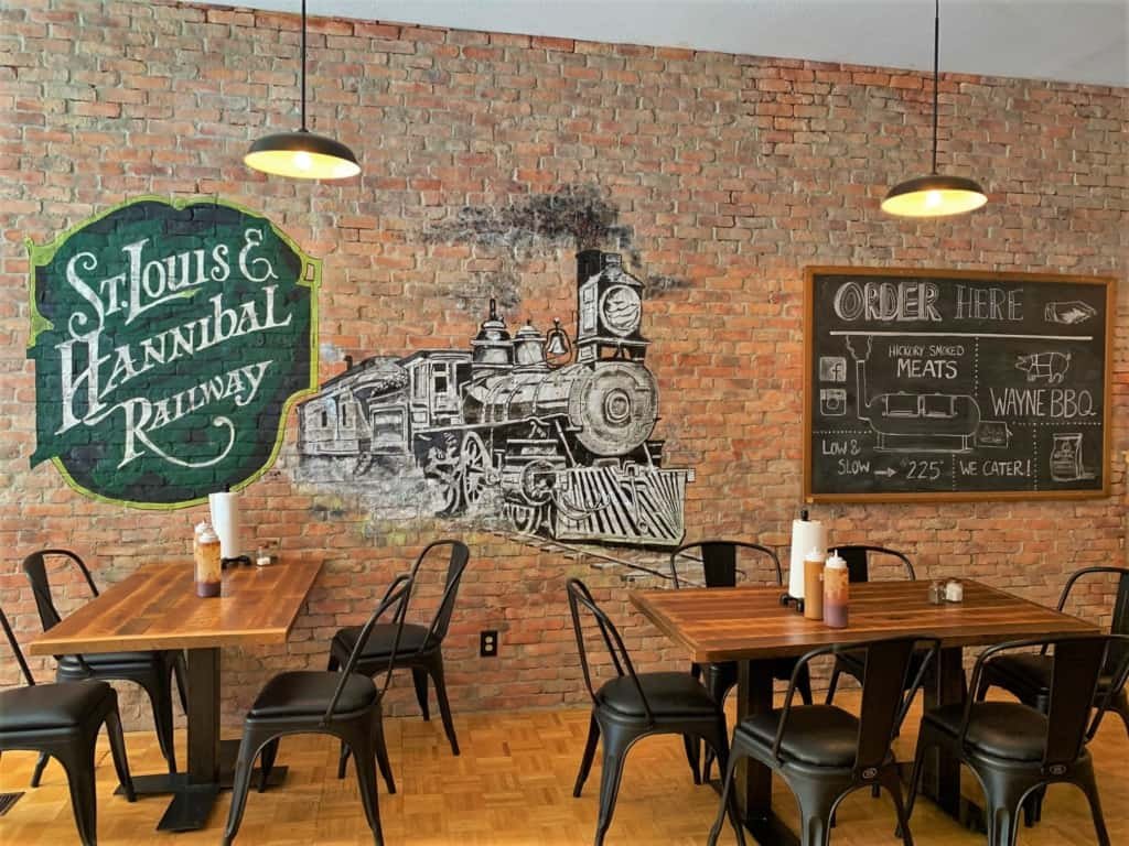 the exposed brick wall makes a good canvas for decorating the interior of Wayne's BBQ in Hannibal, Missouri.