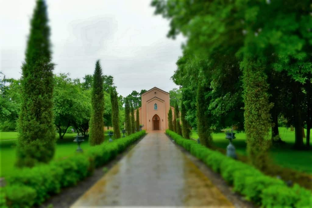 A row of manicured bushes leads visitors to the Precious Moments Chapel.