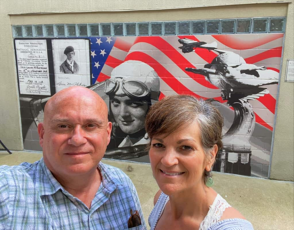 The authors pose in front of a local mural that touts the airborne inspiration brought by Louise Thaden.